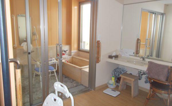 個浴 引き戸や手すりなどの設置と木質の壁材と浴槽が心地よく浴室を利用する事が出来ます。(シニアあしたば)