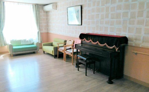 談話スペース 大きな窓が開放的で広い空間にソファーやピアノが配置されて快適に利用する事が出来ます(やすらぎの郷 見付)