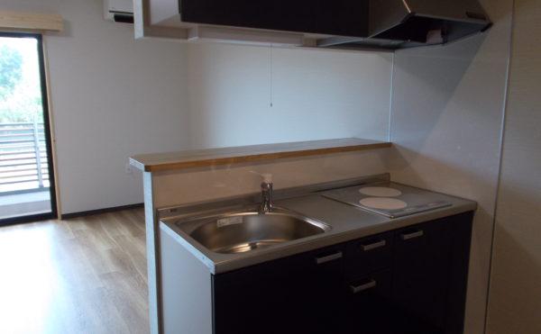 IHコンロの対面キッチン 人気の対面カウンター式キッチンで扉もダーク色でお洒落になっています。(glad 下川原)
