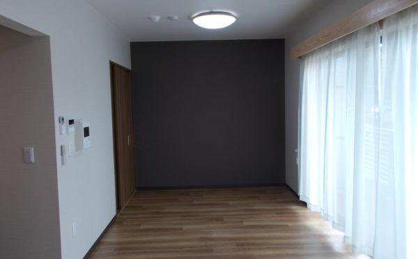 お洒落な室内 一面だけダークなアクセントクロスを使用することでお洒落で高級感のある空間になります。 (glad 下川原)