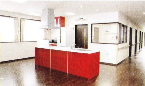 キッチン ダーク色の床材に明るいトーンのキッチンが綺麗に調和している空間になっています。(グループホームつどい)