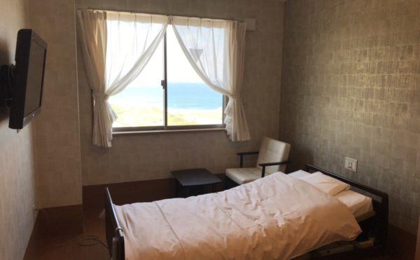 居室 壁掛テレビが設置され、大型のベッドとソファーと快適な空間です。(ナーシングホーム静養館御前崎オーシャンビュー)