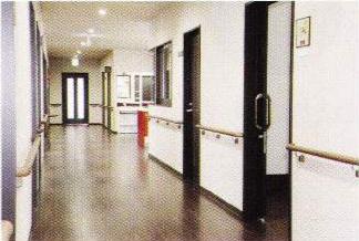 広い廊下 広い廊下には、床材に合わせたダーク色の手すりと腰壁材が調和された内装になります。(グループホームつどい)