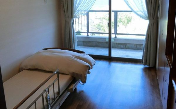 一人部屋の居室です。大きな窓が配置されていてベッドも設置されて、快適に過ごす事が出来ます。(スカイテラス伊東)