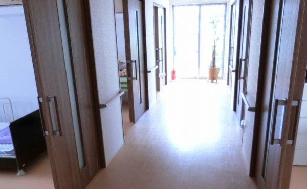 広い廊下 段差がなく大きな引き戸の扉が設置され、各所に手すりのある明るくて広い廊下です。(グループホームつどい)