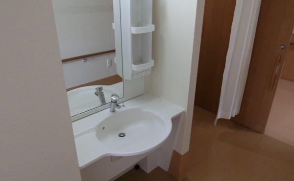 最新の洗面 車イスの方でも利用しやすい洗面でホワイト色の清潔な設備です。(ロータスケア緑ヶ丘)