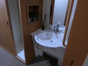 居室洗面 清潔感のあるホワイト色の洗面台で、シングルレバーと新しい設備が快適に利用できます。(ミモザ熱海湯庵)