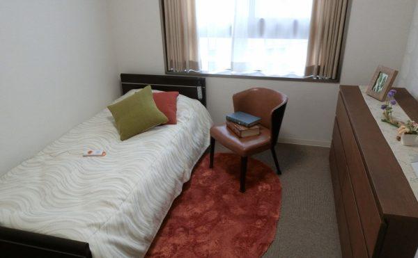 モデルルーム① 床はお洒落なカーペット仕上げでベッド、防炎カーテン、チェスト等の家具付きです。(ミモザ熱海湯庵)