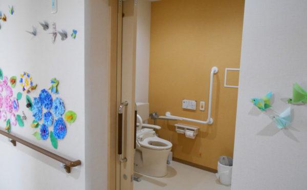 共有トイレ① 清潔感があり、広いトイレスペースには適所に手すりが配置されていて安心です。(クオリティリビングおかりや)