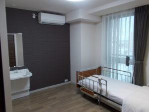居室 ダークなカーテン柄やアクセントクロスを貼り、高級感のある居室に仕上がっています。(コルディアーレ藤枝)