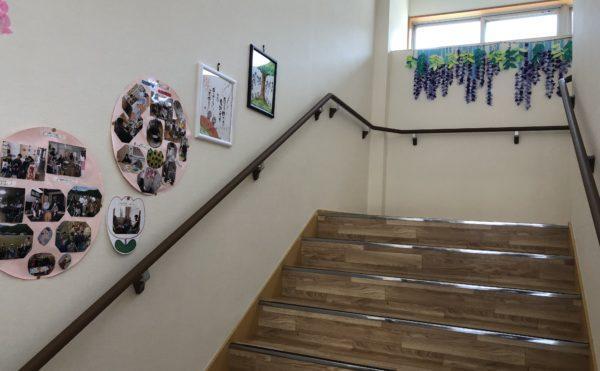 広い階段。両側に手すりが設置され、掲示物が楽しみの広い階段になります。(グループホーム ケアクオリティ おかりや)