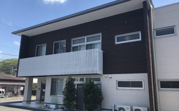 外観② 正面玄関のファサードは、ステン色のサッシや格子バルコニーが綺麗です。(グループホーム ケアクオリティ おかりや)