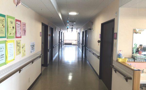 死角のない廊下① 直線の廊下には大きな窓が設置されて楽しく移動することが出来ます。(アレンジメントケア桜ヶ丘)